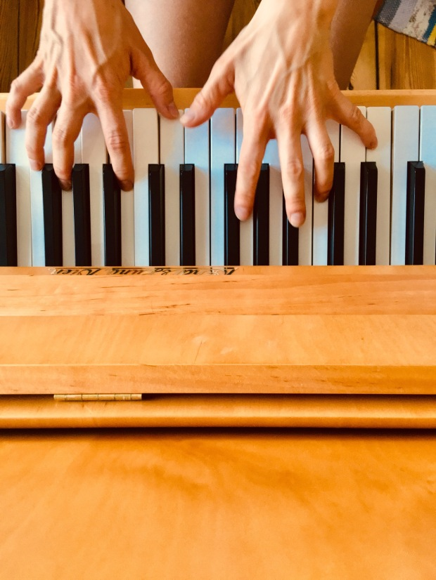 View on a bright wooden piano: the black and white keys are played by two hands